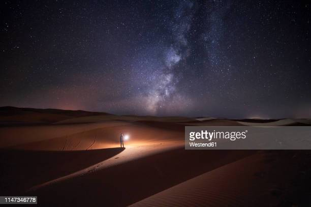 morocco, man with light at night in merzouga desert - desert stock pictures, royalty-free photos & images