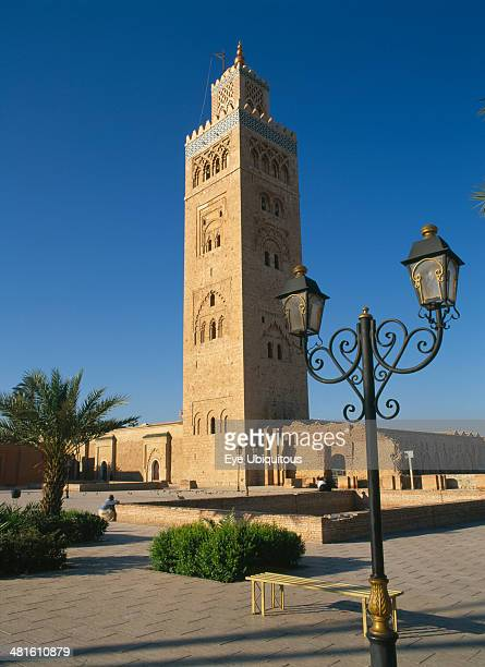 Morocco Marrakech Koutoubia Mosque tower seen from pavement with blue sky behind and street lamps in foreground