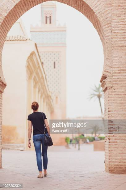 morocco, marrakesh, back view of woman looking at kasbah mosque - femme marocaine photos et images de collection