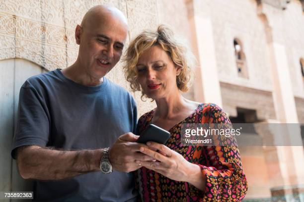 Morocco, Marrakesh, couple looking at cell phone