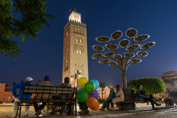 Morocco, Marrakesh, Koutoubia mosque at night. Street sellers resting in front of the minaret