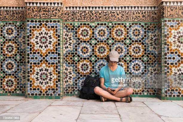 morocco, marrakesh, tourist sitting at tiled wall looking at cell phone - nordafrika stock-fotos und bilder
