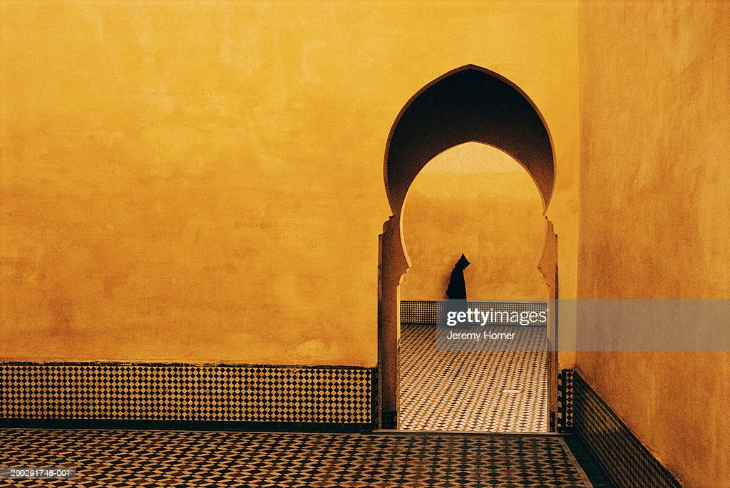 Morocco, Meknes, person walking by archway : Stock Photo