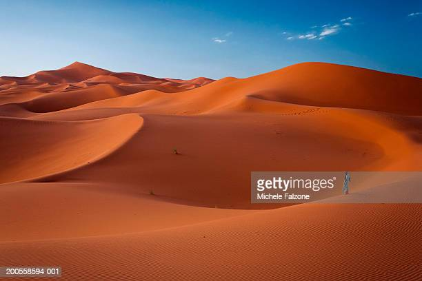 Morocco, Merzouga, Bedouin tribesman walking in sand dunes