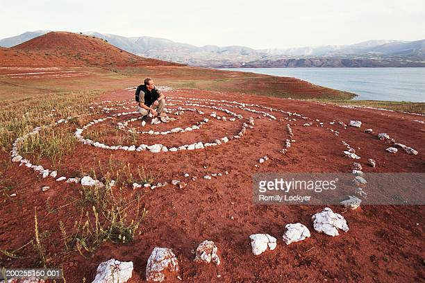 Morocco, Middle-Atlas, young man crouched by stone circles