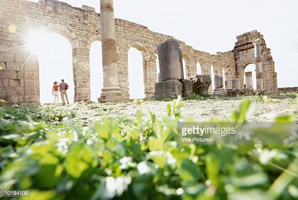 morocco, moulay idriss, roman ruins at volubilis, couple under archway - volubilis fotografías e imágenes de stock
