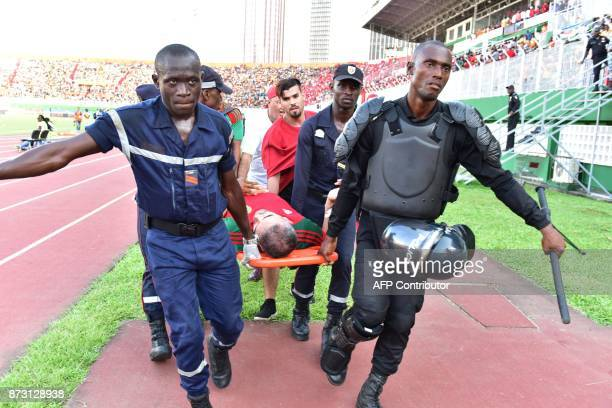 A Morocco team supporter suffering from heat exhaustion is stretchered to a medical tent at the Felix HouphouetBoigny stadium in Abidjan on November...