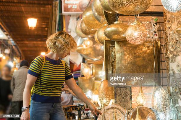 Morocco, woman at a shop with lamps