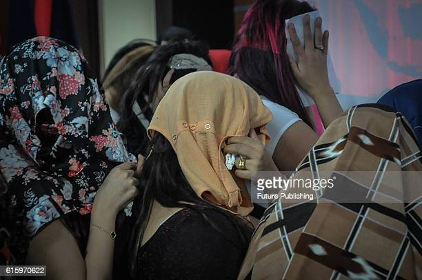 Morocco women's suspected of working as prostitutes cover their faces after their arrest at an immigration office on October 21 2016 in Jakarta...