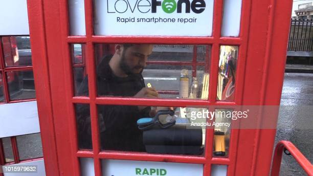 Morocconorigin Fouad Choaibi works inside an iconic Red English Telephone booth used as a phone repair shop at Hollborn district of London United...