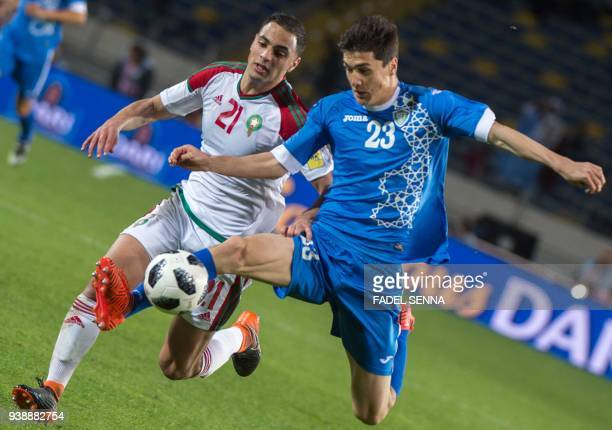 Morocco's Amrabet Soufyan vies for the ball with Uzbekistan's Shomurodov Eldor during their international friendly football match between Morocco and...