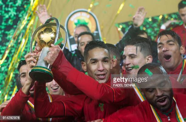 Morocco's Badr Banoun holds up the trophy with teammates as they celebrate after winning the final football match of the African Nations Championship...