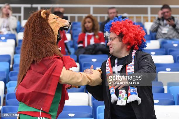 A Morocco's fan dressed as a lion hugs another fan prior to the Russia 2018 World Cup Group B football match between Spain and Morocco at the...