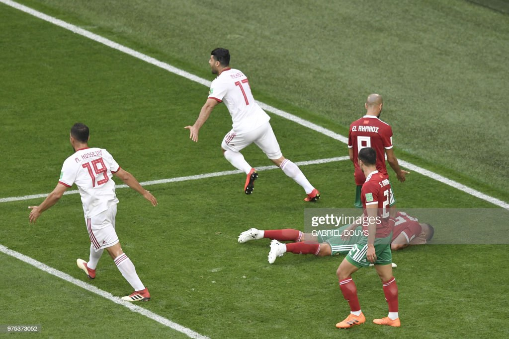 Morocco's forward Aziz Bouhaddouz (R) reacts after scoring an own goal as Iran's defender Majid Hosseini (L) and Iran's forward Mehdi Taremi (2L) celebrate during the Russia 2018 World Cup Group B football match between Morocco and Iran at the Saint Petersburg Stadium in Saint Petersburg on June 15, 2018. (Photo by GABRIEL BOUYS / AFP) / RESTRICTED