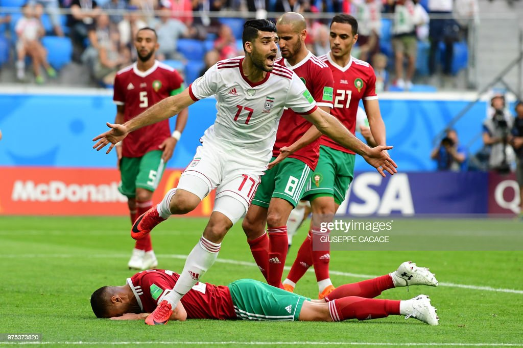 Morocco's forward Aziz Bouhaddouz (down) reacts after scoring an own goal as Iran's forward Mehdi Taremi (up) celebrates during the Russia 2018 World Cup Group B football match between Morocco and Iran at the Saint Petersburg Stadium in Saint Petersburg on June 15, 2018. (Photo by Giuseppe CACACE / AFP) / RESTRICTED