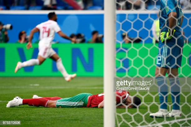 TOPSHOT Morocco's forward Aziz Bouhaddouz reacts after scoring an own goal during the Russia 2018 World Cup Group B football match between Morocco...