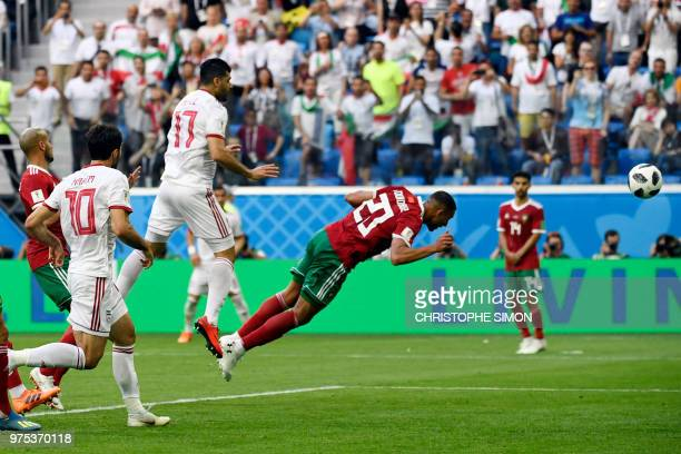 Morocco's forward Aziz Bouhaddouz scores an own goal during the Russia 2018 World Cup Group B football match between Morocco and Iran at the Saint...