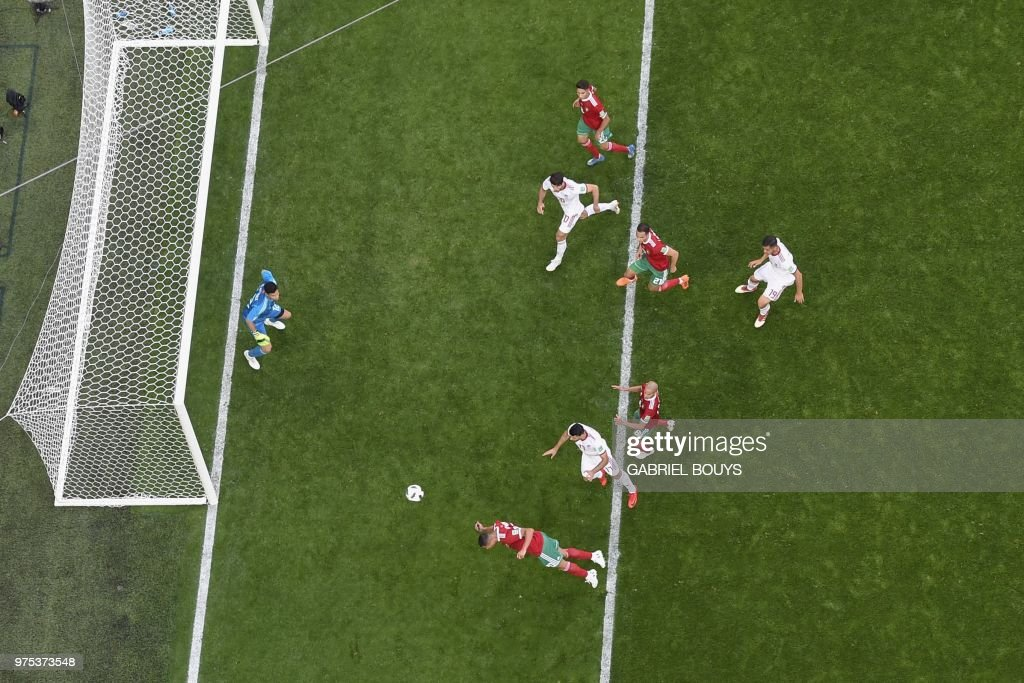 TOPSHOT - Morocco's forward Aziz Bouhaddouz (down) scores an own goal during the Russia 2018 World Cup Group B football match between Morocco and Iran at the Saint Petersburg Stadium in Saint Petersburg on June 15, 2018. (Photo by Gabriel BOUYS / AFP) / RESTRICTED TO EDITORIAL USE - NO MOBILE PUSH ALERTS/DOWNLOADS / The erroneous mention appearing in the metadata of this photo by Gabriel BOUYS has been modified in AFP systems in the following manner: [Morocco's forward Aziz Bouhaddouz ] instead of [Iran's forward Sardar Azmoun]. Please immediately remove the erroneous mention from all your online services and delete it from your servers. If you have been authorized by AFP to distribute it to third parties, please ensure that the same actions are carried out by them. Failure to promptly comply with these instructions will entail liability on your part for any continued or post notification usage. Therefore we thank you very much for all your attention and prompt action. We are sorry for the inconvenience this notification may cause and remain at your disposal for any further information you may require.