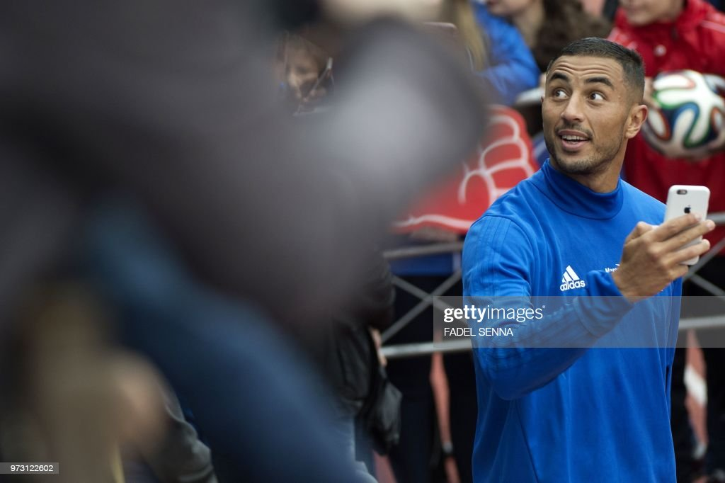 Moroccos forward aziz bouhaddouz takes pictures with his mobile moroccos forward aziz bouhaddouz takes pictures with his mobile phone as fans greet him at the end of a training session of the moroccan national football m4hsunfo