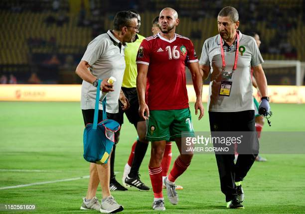 Morocco's forward Nordin Amrabat is escorted off the pitch for treatment during the 2019 Africa Cup of Nations Group D football match between Morocco...