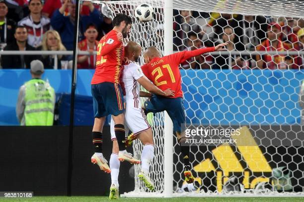 Morocco's forward Noureddine Amrabat jumps for the ball between Spain's midfielder Isco and Spain's forward David Silva during the Russia 2018 World...