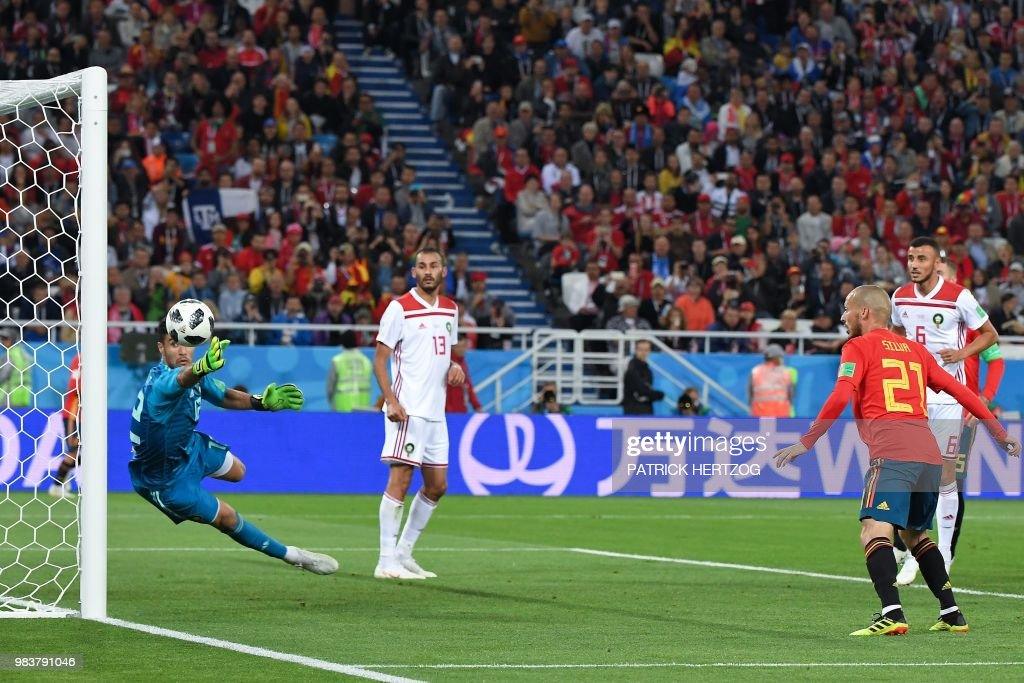 TOPSHOT - Morocco's goalkeeper Munir Mohand Mohamedi (L) saves a goal attempt by Spain's forward David Silva (2R) during the Russia 2018 World Cup Group B football match between Spain and Morocco at the Kaliningrad Stadium in Kaliningrad on June 25, 2018. (Photo by Patrick HERTZOG / AFP) / RESTRICTED