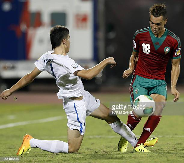 Morocco's Hamza Sakh fights for the ball against Uzbekistan's Akramjon Komilov during their FIFA U17 World Cup 2013 football match in the United Arab...