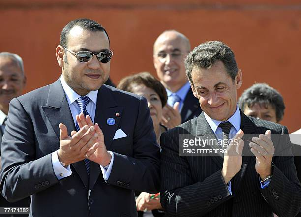 Morocco's King Mohammed VI applauds beside French President Nicolas Sarkozy during a visit to a center for delinquents 24 October 2007 in Marrakech....