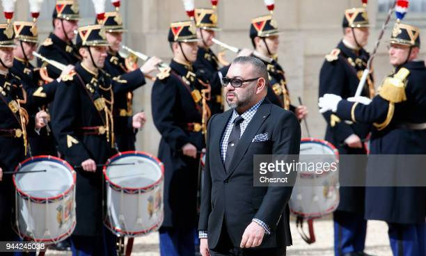 Morocco's King Mohammed VI walks past the honor guard as he arrives for a meeting with French President Emmanuel Macron at the Elysee Presidential...