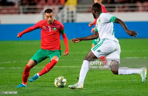 Morocco's midfielder Hakim Ziyech vies for the ball with Mauritania's midfielder Hacen El Ide during the 2021 Africa Cup of Nations group E...