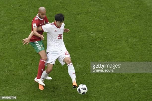 Morocco's midfielder Karim El Ahmadi vies for the ball with Iran's forward Sardar Azmoun during the Russia 2018 World Cup Group B football match...