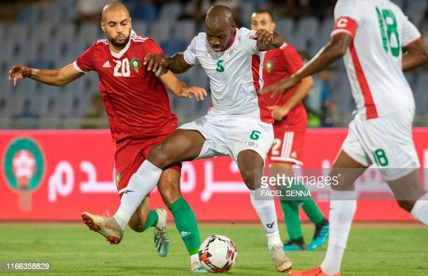 Morocco's midfielder Sofyan Amrabat vies for the ball with Burkina Faso's midfielder Bryan Dabo during the friendly football match between Morocco...