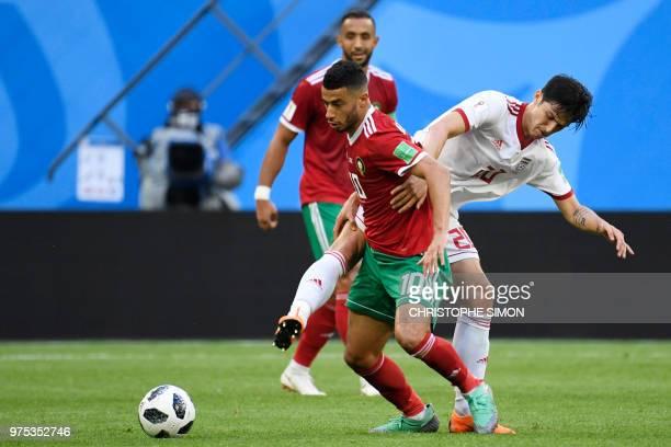 Morocco's midfielder Younes Belhanda challenges Iran's forward Sardar Azmoun during the Russia 2018 World Cup Group B football match between Morocco...