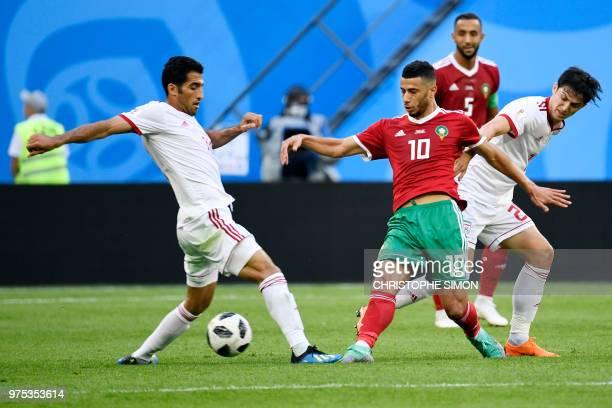 Morocco's midfielder Younes Belhanda challenges Iran's forward Vahid Amiri and Iran's forward Sardar Azmoun during the Russia 2018 World Cup Group B...