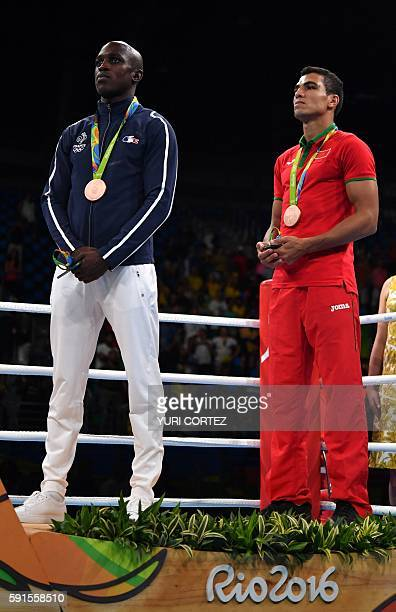 Morocco's Mohammed Rabii and France's Souleymane Diop Cissokho pose for a picture with their medals after the Men's Welter Final Bout match at the...