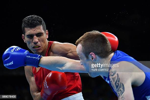 Morocco's Mohammed Rabii blocks a punch by Ireland's Steven Gerard Donnelly during the Men's Welter Quarterfinal 1 at the Rio 2016 Olympic Games at...
