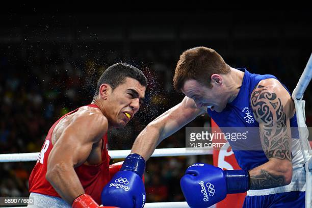 Morocco's Mohammed Rabii is punched by Ireland's Steven Gerard Donnelly during the Men's Welter Quarterfinal 1 at the Rio 2016 Olympic Games at the...