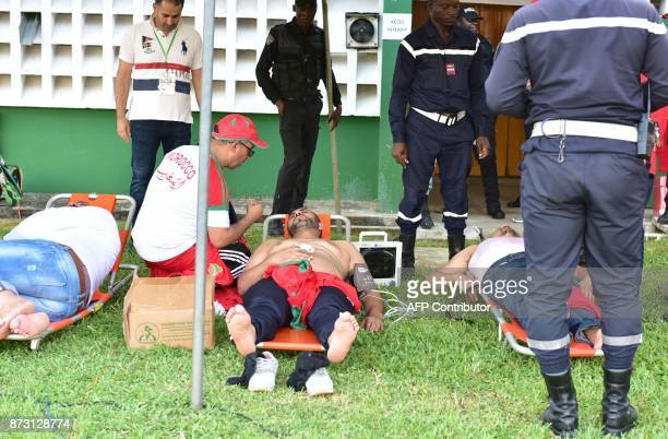 Morocco's team supporters suffering from heat exhaustion receive medical care at the Felix HouphouetBoigny stadium in Abidjan on November 11 during...