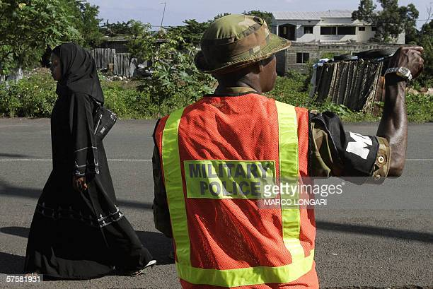 A Nigerian military policeman part of the Africa Union mission to Comoros gestures while a woman passes by in Moroni Comoros 11 May 2006 tHE AMISEC...