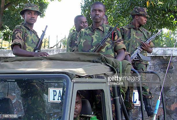Soldiers from the African Union stand guard next to a pollng station in Moroni as Comorans queue to cast their ballots as the Islands of Grande...
