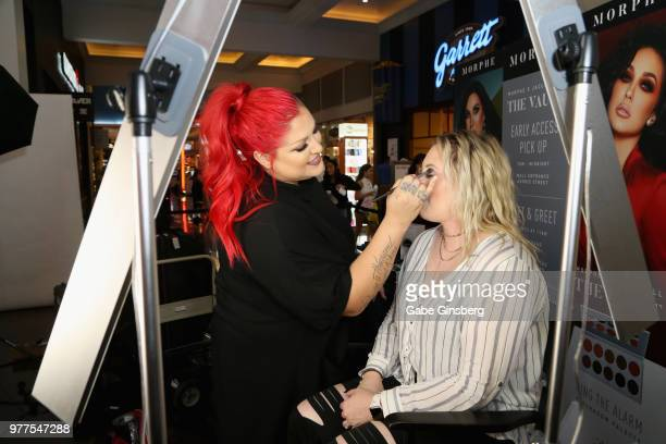 Morphe Director of Global Artistry Nicole Faulkner applies makeup to a customer during the Morphe store opening at the Miracle Mile Shops at Planet...
