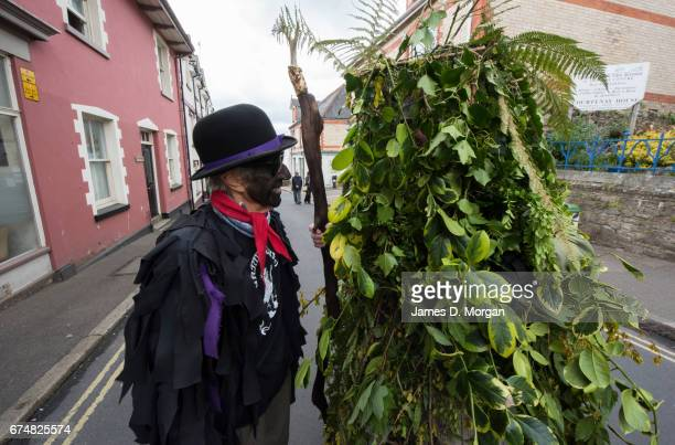 Morris dancer with his face painted black as part of a traditional disguise looks at a man dressed in a tree foilage costume at the Green Man Spring...