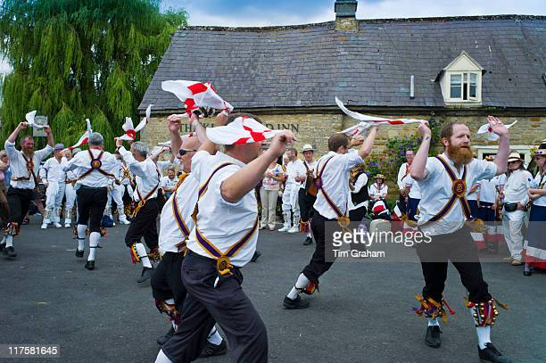 Morris dancers Brighton Morris Men perform a dancing display at The Kings Head Pub in Bledington Oxfordshire UK