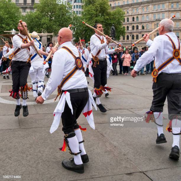 morris dancers clashing sticks in trafalgar square, london - morris dancing stock photos and pictures