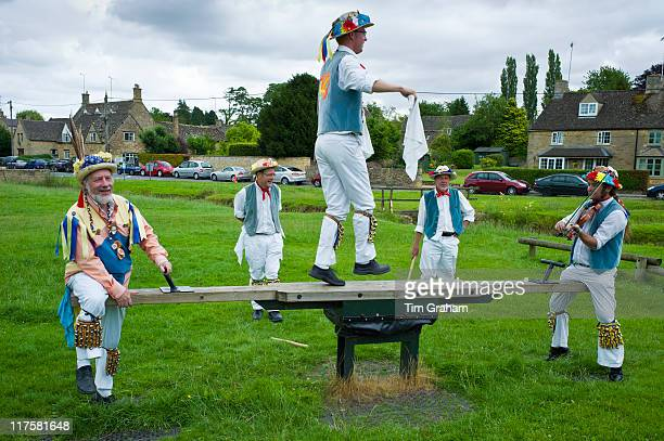 Morris dancers Icknield Way Morris Men in children's playground at The Kings Head Pub Bledington Oxfordshire UK