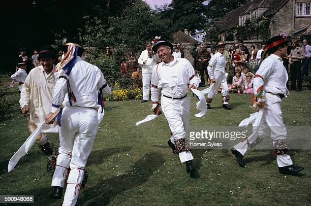 Morris dancers wearing the traditional white costumes with bells strapped around their legs and holding handkerchiefs dance during a festival in...