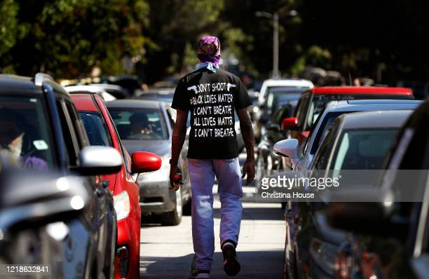 Morris Griffin walks between rows of cars before a procession departs Leimert Park for downtown Los Angeles for a memorial service to honor George...