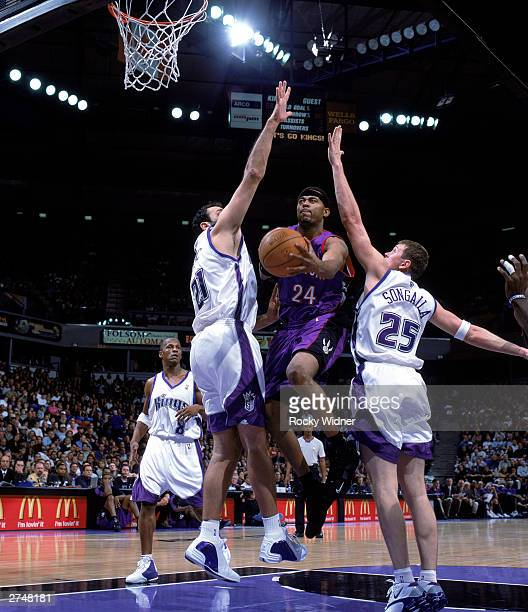 Morris Peterson of the Toronto Raptors drives to the basket between Vlade Divac and Darius Songaila of the Sacramento Kings during the NBA game at...