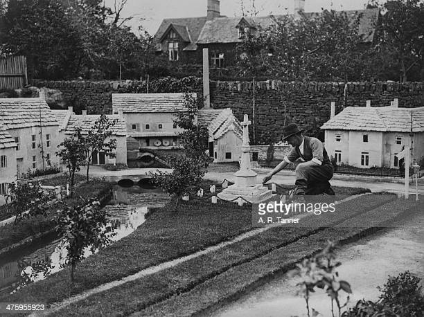C A Morris putting the finishing touches to a miniature war memorial in the model village he has constructed in the garden of his home in at...