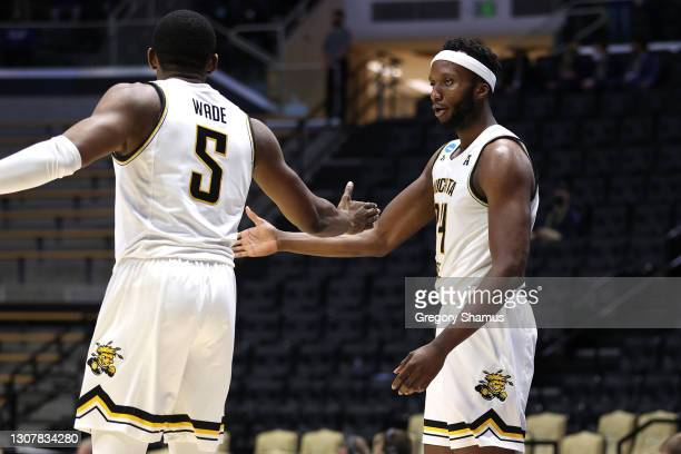 Morris Udeze of the Wichita State Shockers celebrates with Trey Wade against the Drake Bulldogs during the second half in the First Four game prior...
